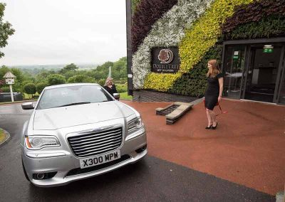 An executive walking towards a private car in south west UK