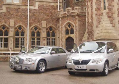 two silver, decorated wedding cars outside a luxury venue near Bath UK