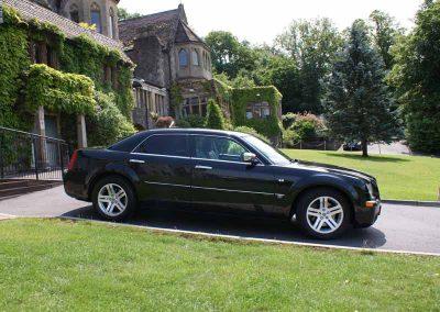 A black 4 seater crysler sedan car outside a luxury hotel near Bristol