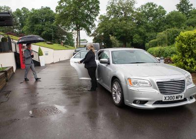 A chauffeur holding open a car door for a business executive in south west England, UK