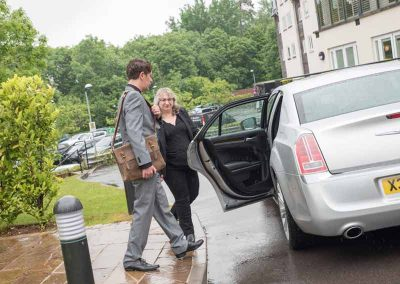 A chauffuer holds a car door open for a client inear Bristol UK