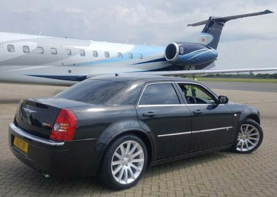 A luxury chauffeur driven car on the tarmac at bristol airport to illistrate airport transfers in south west UK