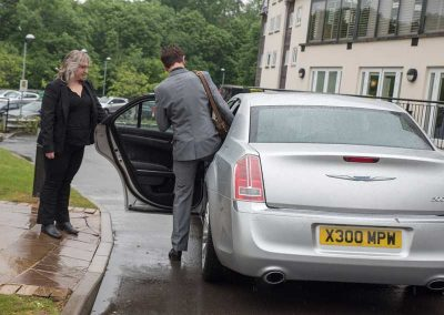 A businessman getting into a professionally driven car near Bristol UK