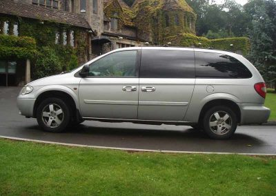 A silver grand voyager 6 seater chauffeur driven car outside a wedding venue near Bristol