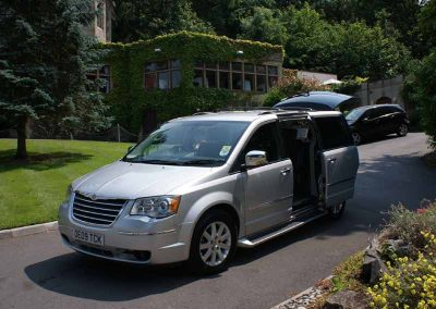 A silver 6 setaer grand voyager people carrier with open doors, showing the luxury interior outside a hotel in weston supermare