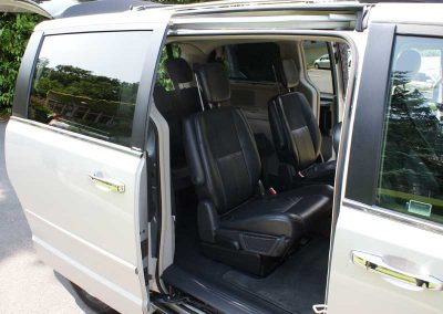 A silver 6 seater grand voyager with open doors looking into the luxury interior where a business passenger might sit