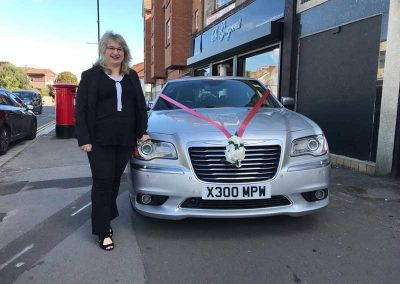 the owner of cadbury cars standing close to an affordable wedding car
