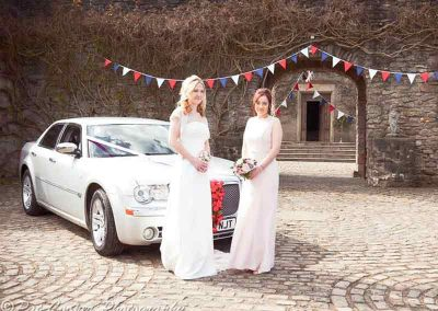 A bride and her bridesmaid standing by an affordable wedding car at a venue near Bristol UK
