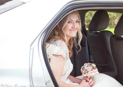 A bride smiling and sitting in her wedding car in north somerset uk