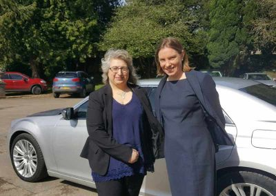 A female business executive with her chauffeur standing in front of a chauffeur driven car near Bath UK