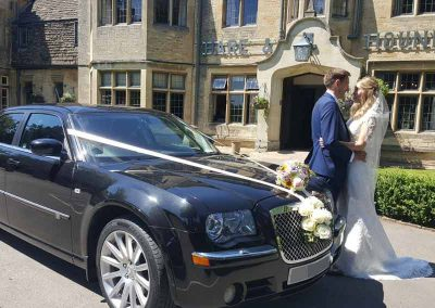bride and groom leaving a chauffeur driven car to go to the venie near Bristol UK