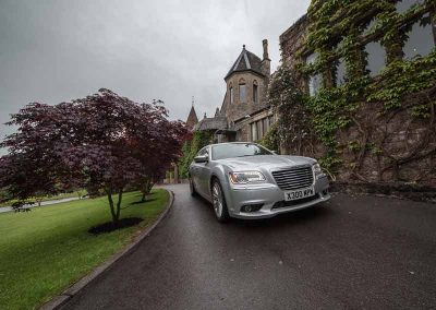 A professionally driven luxury car waiting for a business executive outside a hotel in North somerset UK