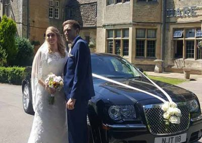 Bride and groom standing by their chauffeur driven wedding car