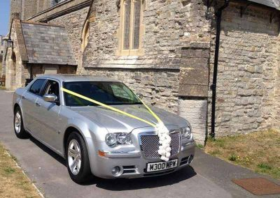 Modern silver wedding car outside a church near Bath UK