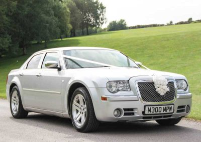 Silver wedding car on the road transporting a bride and groom to their big day in north somerset uk