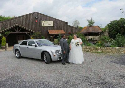 wedding couple standing by a luxury affordable weeding car in south west England UK
