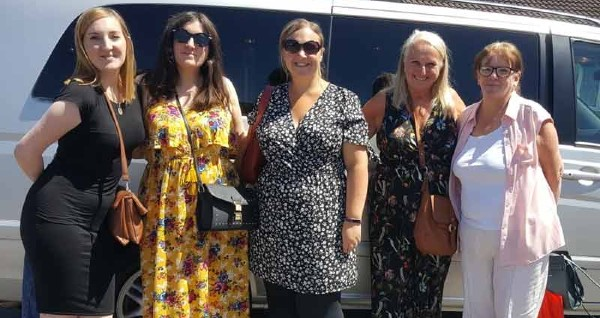 A group of women standing beside a chauffeur driven 7 seater people carrier on their way to a shopping trip in south west uk